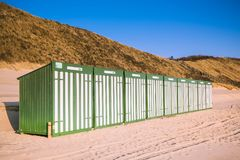 Green and white beach huts. A row of beach huts on a beach in Zoutelande inZeeland,  The Netherlands. Photographed at sunset Stock Image