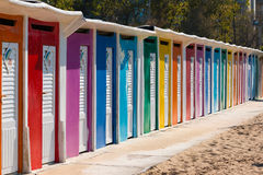 A row of beach huts with brightly coloured doors on sandy beach Stock Photos