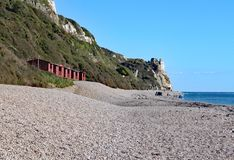 A row of beach huts on the shingle beach at Branscome in Devon, England. This is accessible by walking the coastal path stock photography