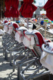 Row of Beach Loungers with Beach Towels and Closed Beach Umbrellas. Row of red beach umbrellas that are closed shut stand next to row of red and white beach Stock Photo