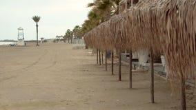Row of beach umbrellas on empty abandoned deserted beach during off-season. Broken. Row of beach umbrellas on empty abandoned deserted beach during off-season on stock video footage
