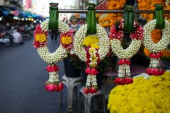 Row of beautiful fresh handmade flower garlands made of white gardenia and crown flower and red rose in Thai style. Hanging on pandan leaves with morning market Stock Image