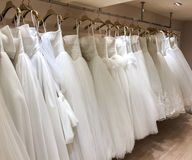 Row of Beautiful Variety Style of Modern and Vintage White Bride Dresses Hanging from the ceiling for Selection of Bride royalty free stock photos