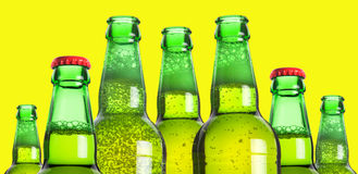 Row of beer bottles. On a yellow background stock photography