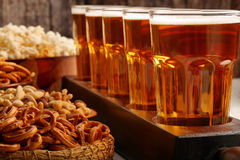 Row of beer glasses and snacks on wooden background football fan Royalty Free Stock Photography