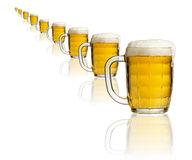 A row of beer mugs. A row of beer mugs full of beer with froth Royalty Free Stock Photos