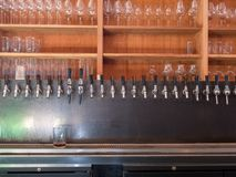 Row of beer taps in back of bar with glasses on shelf Royalty Free Stock Photography