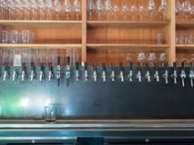 Row of beer taps in back of bar with sunny light stock photography