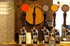 Row of Beer Taps in Bar. Close Up of Row of Shiny Beer Taps of Different Brews in Bar stock photography