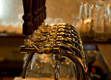 Row of beer taps in a pub or bar. Row of stainless steel beer taps for dispensing draught beer from the metal storage kegs in a pub or bar at a nightclub royalty free stock images