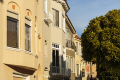 A row of beige upscale houses against blue sky. A row of beige upscale houses with balcony detail against a blue sky. Some trees can be seen, as well as some Stock Image