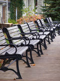 Row of benches in the autumn. Eight benches in a row along a street in a  mountain town Royalty Free Stock Photography