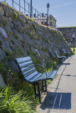 A row of benches in front of Varbergs Fästning. A row of benches in front of the stone walls of Varbergs Fästning (the Fortress of Varberg), a historic Stock Photo