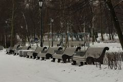Row of benches in the park. A row of benches in a snow-covered winter park Stock Photos