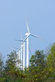 Row of big windturbines behind trees Royalty Free Stock Images