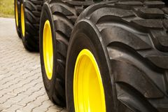 Row of big yellow truck wheels background. Huge industrial tractor tires royalty free stock photo