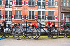 Row of bikes and dutch traditional houses on background in Amsterdam Stock Image