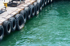 Row of black car tires used as boat bumpers Royalty Free Stock Photos