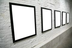 Row of black frames on white brick wall Stock Image