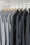 Row of black and grey shirts hanging on coat hanger Stock Images