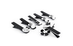 Row of black hair clips on white Stock Images