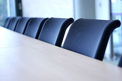 View of row of office chairs in a meeting room. Row of black office chairs in a meeting room with white board in the distance stock photography