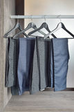 Row of black pants hangs in wardrobe at home Stock Images