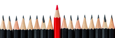 Row of black pencils with one red pencil in middle Royalty Free Stock Photos