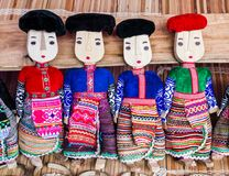 Row of black and red Dzao wooden dolls. Wearing traditional clothes, Can Cau market, northern Vietnam Royalty Free Stock Photography