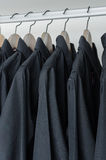 Row of black shirts hanging on coat hanger Royalty Free Stock Images