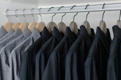 Row of black shirts hanging on coat hanger Stock Image