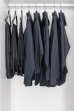 Row of black shirts and pants hanging on coat hanger Stock Images