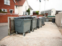 A row of black waste bins outside full. England; UK Stock Images