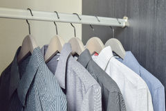 Row of black and white shirts hanging in wardrobe Stock Image