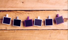 Row of blank instant photo frames on a string. Row of blank instant photo frames hanging from pegs on a string graduating from white to purple on a rustic wood stock photography