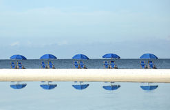 Row of blue beach umbrellas and chairs royalty free stock photos