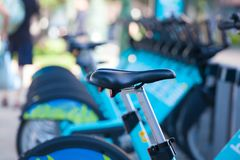 Row of blue bikes parked on city sidewalk. Focus on front most bike seat Stock Photos