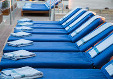 Row of Blue Chaise Lounges with Blue Spa Towels. Rows of chaise lounges at a spa with blue towels stock photos