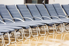 Row of Blue Chaise Lounges in Rain Stock Photo