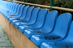 Row of blue plastic seats mounted on top of concrete bleachers with metal fence and trees in background next to basketball court. On wet rainy day royalty free stock images