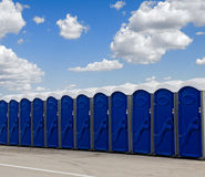 A row of blue portable toilets. Blue sky and white clouds background royalty free stock photo