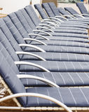 Row of Blue and Silver Chaise Lounges after Rain Royalty Free Stock Photo