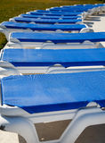 Row of Blue Vinyl Chaise Lounges. Row of blue and white plastic chaise lounges around a swimming pool stock image