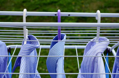 Row of blue, white shirts drying Royalty Free Stock Photo
