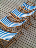 Row of blue and white striped beach chairs Royalty Free Stock Photos