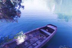 Row boat in calm blue water. Row boat in calm blue and clear water Stock Photography
