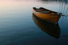 Row boat in calm water. Wodden row boat in calm blue water Stock Photography