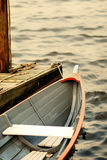Row boat at the dock 02. A row boat tied to the dock in a river. The hull of the boat stock image