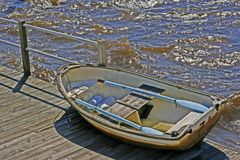 A row boat on a dock with blue oars. A small row boat sitting on a dock with blue oars on the seats, surrounded by waves in the background Stock Photography