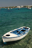Row boat in harbor. An old wood row boat in the harbor with hotels in the distance in the greek islands Royalty Free Stock Photography